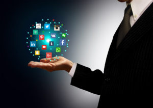 Businessman holding hologram with social media network icons - Social media networks concept including Google Plus, Facebook, Twitter, Pinterest, Instagram, Youtube and other major industry players