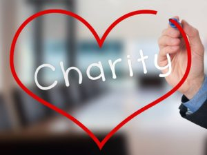 Hand writing Charity inside heart shape. Charity concept. Isolated on office. Stock Image