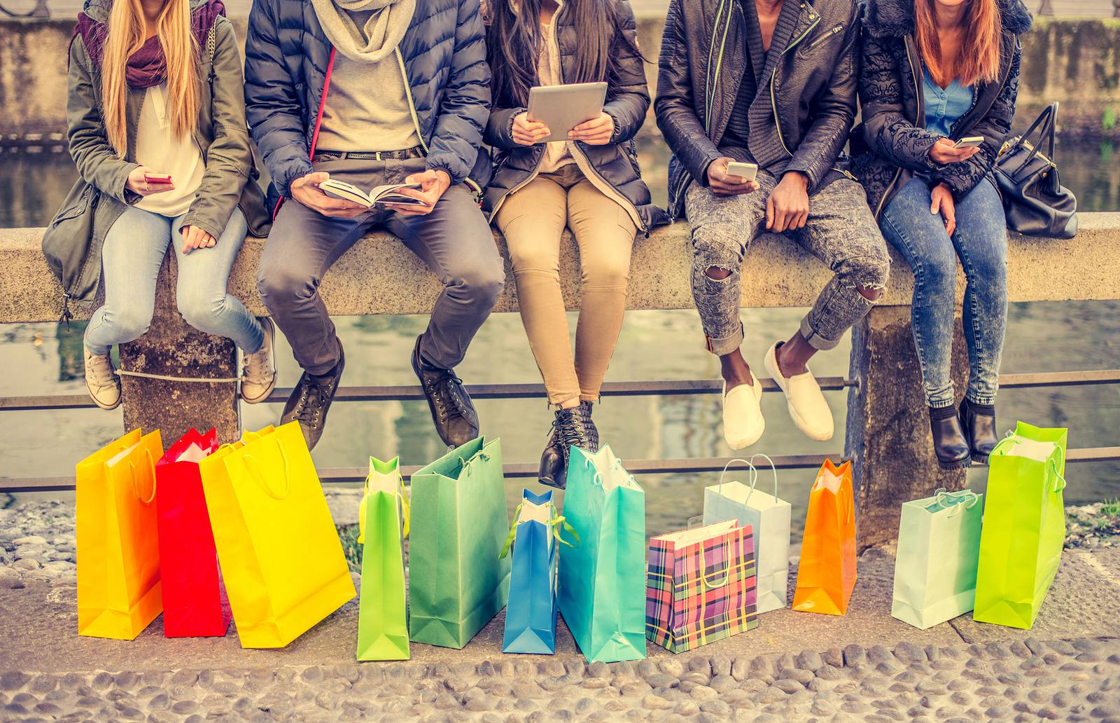 Group of friends sitting outdoors with shopping bags - Several people holding smartphones and tablets - Concepts about lifestyleshoppingtechnology and friendship